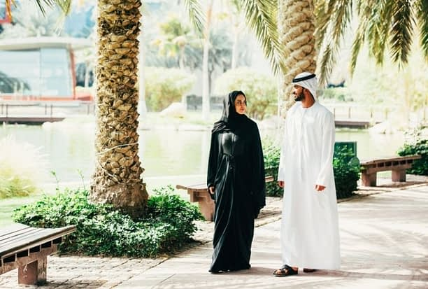 Emirati man and woman walking in the UAE wearing traditional clothes